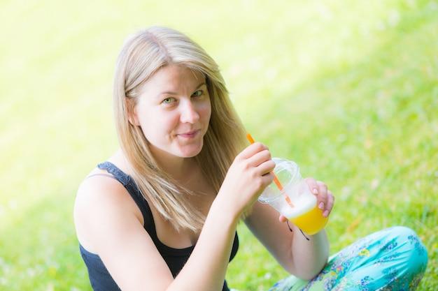 Mulher loira, bebendo, suco fruta, em, parque