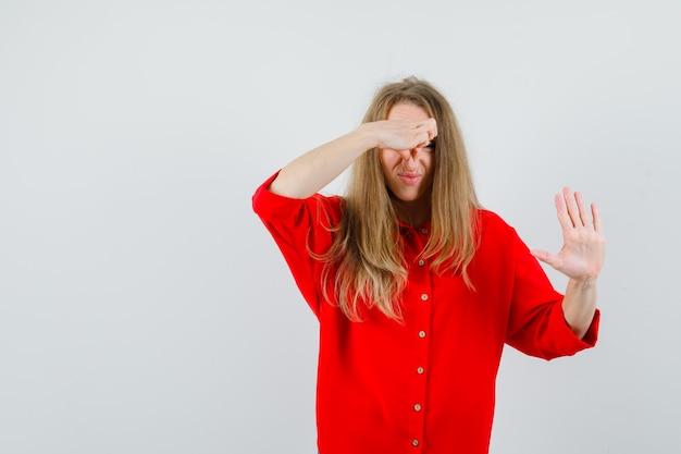 Mulher loira beliscando o nariz devido ao mau cheiro na camisa vermelha e parecendo enojada.