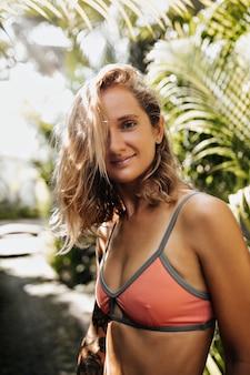 Mulher loira bem encaracolada com top laranja sorrindo e olhando para a frente