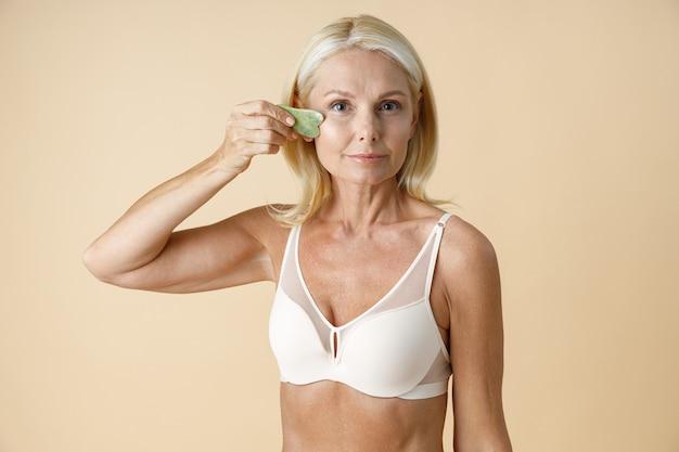 Mulher loira bem madura com pele perfeita e brilhante olhando para a câmera segurando uma massagem jade gua sha