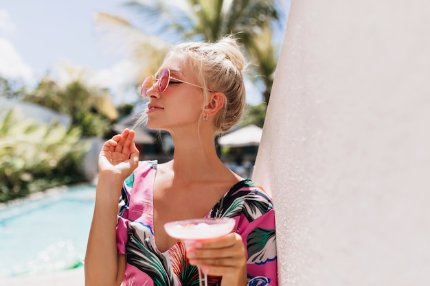 Mulher loira bonita aproveitando o sol no resort.