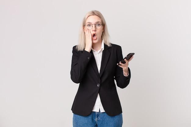 Mulher loira bonita chocada e assustada segurando um telefone celular