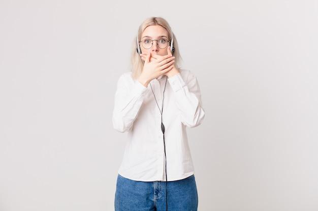 Mulher loira bonita cobrindo a boca com as mãos com um conceito de telemarketing chocado