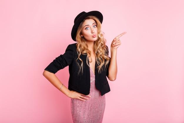 Mulher loira bonita com cara de surpresa apontando pelo dedo em alguma coisa, em cima de parede rosa. usando vestido moderno com seqüência, jaqueta preta e chapéu.