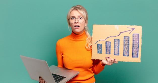 Mulher loira bonita com um gráfico de barras crescente e um laptop