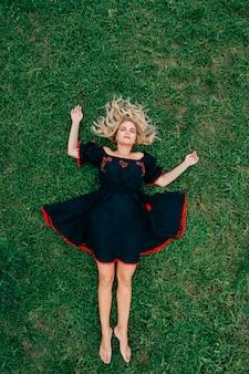 Mulher loira bonita de vestido de linho étnico preto deitado na grama verde.