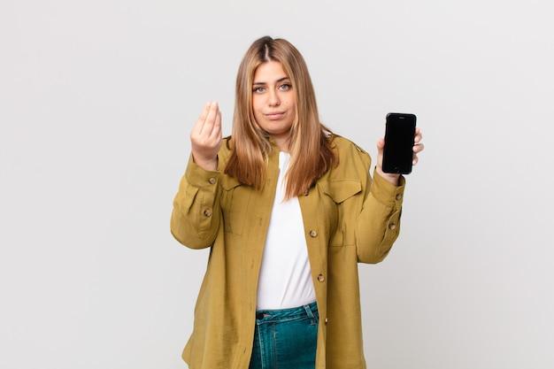 Mulher loira bonita e curvilínea fazendo um gesto de capice ou dinheiro, dizendo para você pagar e segurando um smartphone
