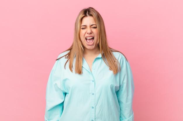 Mulher loira bonita e curvilínea gritando agressivamente, parecendo muito zangada