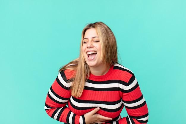 Mulher loira bonita e curvilínea rindo alto de alguma piada hilária