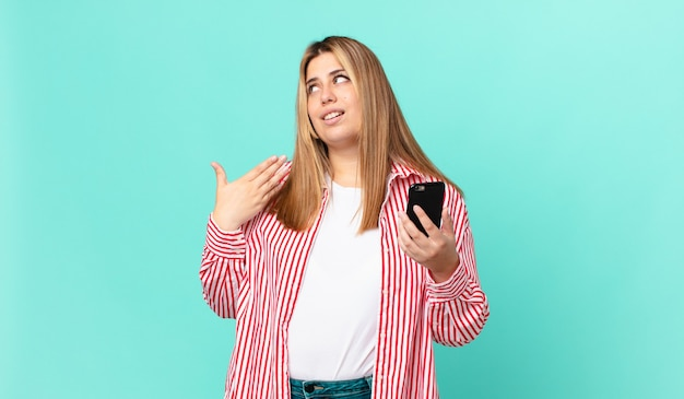 Mulher loira bonita e curvilínea se sentindo estressada, ansiosa, cansada e frustrada e segurando um smartphone