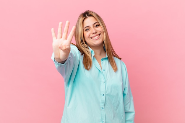 Mulher loira bonita e curvilínea sorrindo e parecendo amigável, mostrando o número quatro
