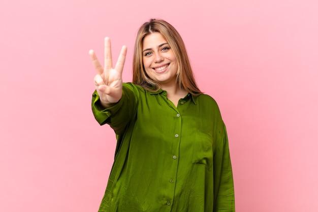 Mulher loira bonita e curvilínea sorrindo e parecendo amigável, mostrando o número três