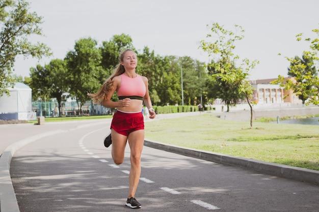 Mulher loira bonita e desportiva com cabelo comprido correndo no parque