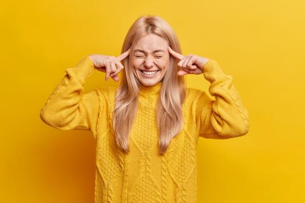 Mulher loira bonita e engraçada fecha os olhos e sorri amplamente, mantendo os dedos indicadores nas têmporas tentando memorizar algo