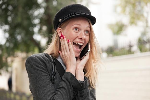 Mulher loira bonita e feliz, mantendo a palma da mão na bochecha e erguendo as sobrancelhas de forma espantosa com a boca bem aberta enquanto ouve notícias surpreendentes por telefone