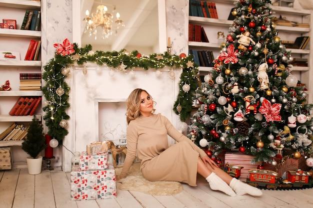 Mulher loira bonita e fofa em um vestido aconchegante e meia sentada perto das caixas de presente de uma lareira e uma árvore