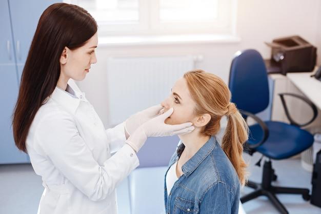 Mulher loira bonita e simpática sentada em frente ao médico e olhando para ela durante o exame médico