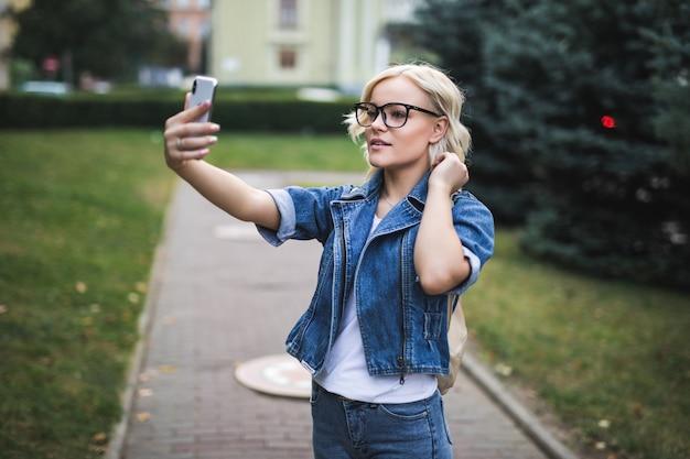 Mulher loira bonita elegante e feliz na suíte jeans faz selfie no telefone na cidade pela manhã