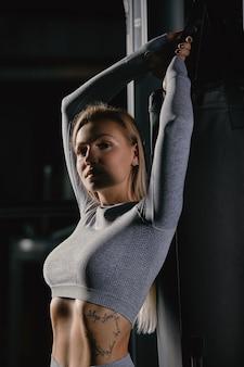 Mulher loira bonita fitness está de pé perto de aparelhos de treino e posando