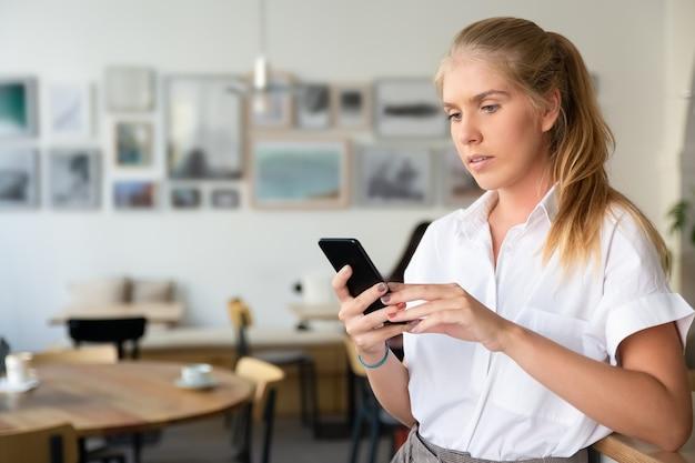 Mulher loira bonita focada vestindo camisa branca, usando smartphone em pé no espaço de trabalho