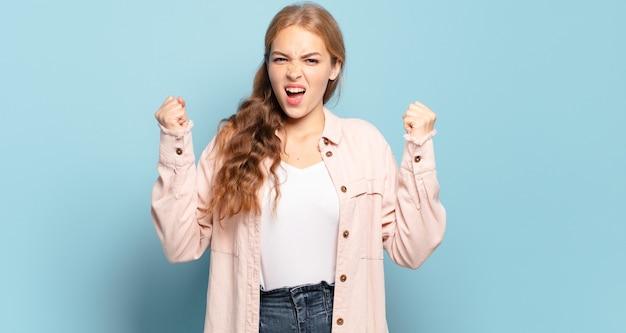Mulher loira bonita gritando agressivamente com uma expressão de raiva ou com os punhos cerrados celebrando o sucesso