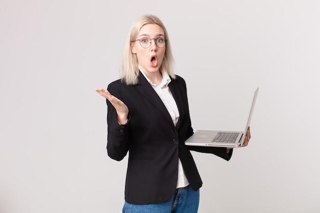 Mulher loira bonita maravilhada, chocada e atônita com uma surpresa inacreditável e segurando um laptop