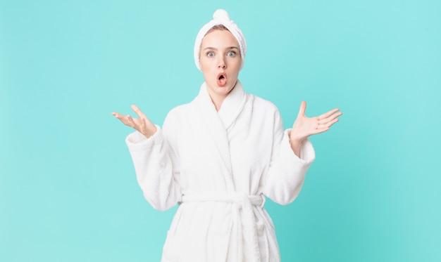 Mulher loira bonita maravilhada, chocada e atônita com uma surpresa inacreditável e vestindo um roupão de banho