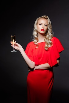 Mulher loira bonita no vestido de noite posando, segurando copo de champanhe