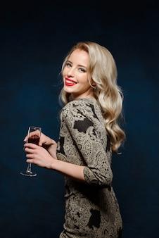 Mulher loira bonita no vestido de noite, sorrindo, segurando o copo de vinho
