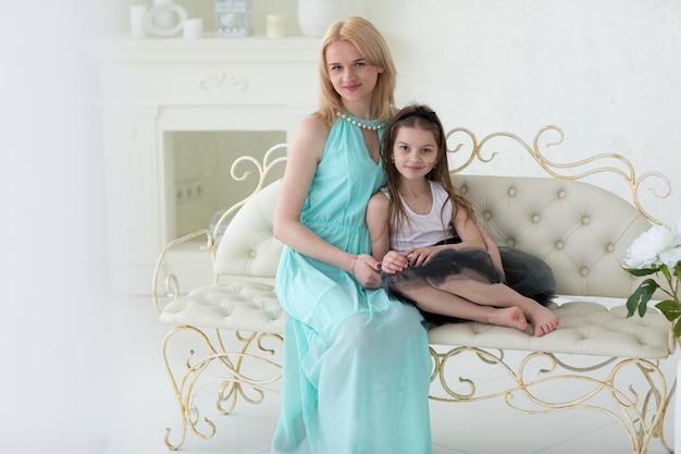 Mulher loira bonita no vestido grego da marinha com a filha