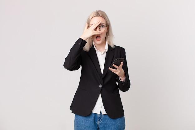 Mulher loira bonita parecendo chocada, assustada ou apavorada, cobrindo o rosto com a mão e segurando um telefone celular