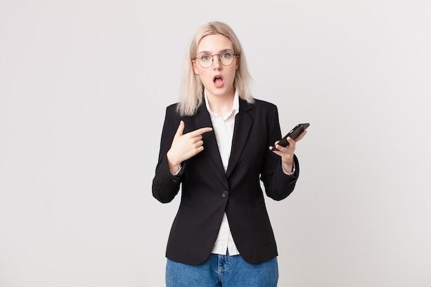 Mulher loira bonita parecendo chocada e surpresa com a boca bem aberta, apontando para si mesma e segurando um telefone celular