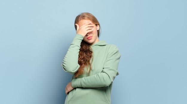 Mulher loira bonita parecendo estressada, envergonhada ou chateada, com dor de cabeça, cobrindo o rosto com a mão
