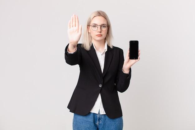 Mulher loira bonita parecendo séria, mostrando a palma da mão aberta fazendo gesto de pare e segurando um telefone celular