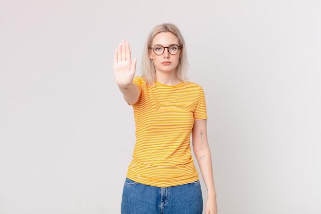 Mulher loira bonita parecendo séria, mostrando a palma da mão aberta fazendo gesto de pare
