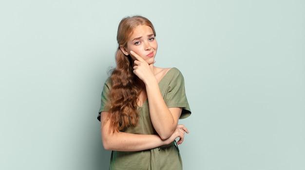 Mulher loira bonita parecendo séria, pensativa e desconfiada, com um braço cruzado e a mão no queixo, opções de peso