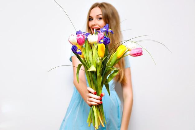 Mulher loira bonita presente a você primavera buquê de flores, tulipas brilhantes, surpresa, engraçado, feriados.