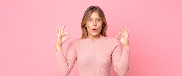 Mulher loira bonita se sentindo chocada, espantada e surpresa, mostrando aprovação e fazendo sinal de ok com as duas mãos