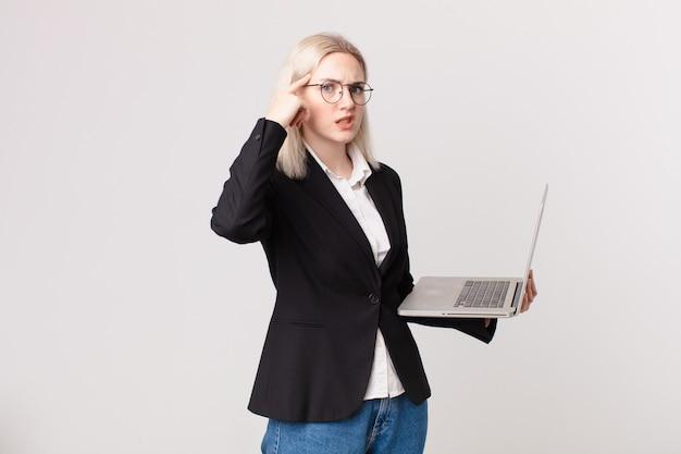 Mulher loira bonita se sentindo confusa e perplexa, mostrando que você é maluca e segurando um laptop