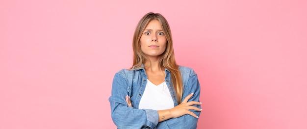 Mulher loira bonita se sentindo descontente e desapontada, parecendo séria, irritada e com raiva de braços cruzados