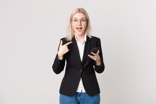 Mulher loira bonita se sentindo feliz e apontando para si mesma com um animado e segurando um telefone celular
