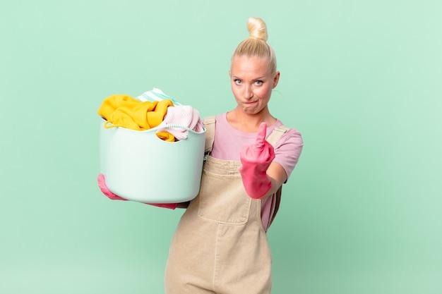 Mulher loira bonita se sentindo irritada, irritada, rebelde e agressiva ao lavar roupa conceito