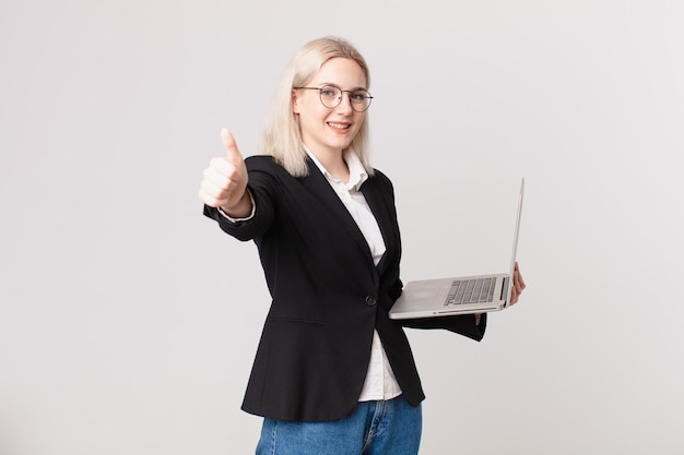Mulher loira bonita se sentindo orgulhosa, sorrindo positivamente com o polegar para cima e segurando um laptop