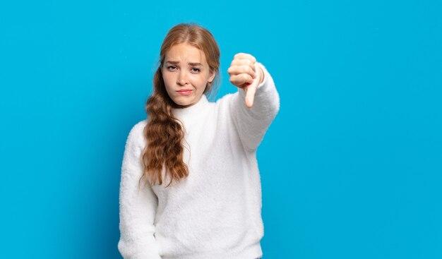 Mulher loira bonita se sentindo zangada, irritada, desapontada ou descontente, mostrando os polegares para baixo com um olhar sério