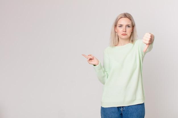 Mulher loira bonita se sentindo zangada, mostrando os polegares para baixo