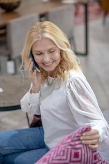 Mulher loira bonita sentada, conversando em um smartphone, olhando para um travesseiro brilhante com um padrão, encantada.