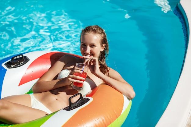 Mulher loira bonita sorrindo, bebendo coquetel, nadar na piscina
