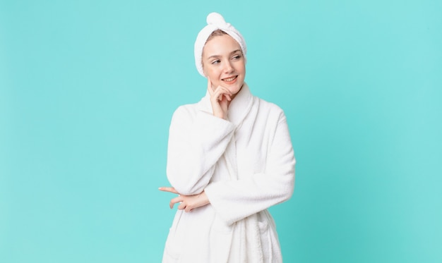 Mulher loira bonita sorrindo com uma expressão feliz e confiante com a mão no queixo e vestindo um roupão de banho