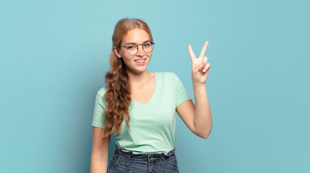 Mulher loira bonita sorrindo e parecendo amigável, mostrando o número dois ou o segundo com a mão para a frente, em contagem regressiva
