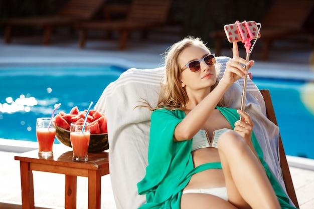 Mulher loira bonita sorrindo, fazendo selfie, deitado perto da piscina